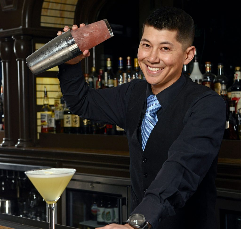 Yoshi Hiraoka prepares a drink behind the bar.