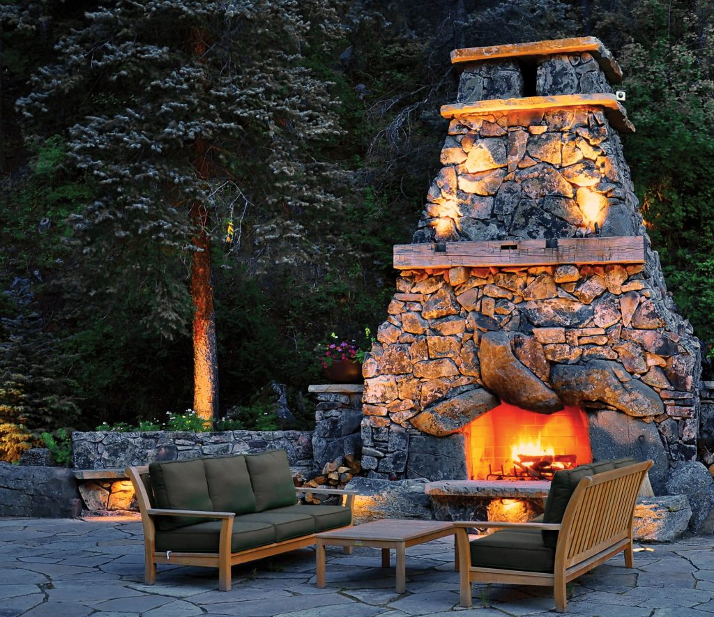 A nighttime view of a beautiful outdoor fire space designed by Designscapes Colorado.